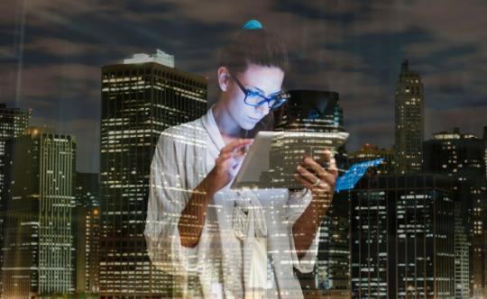 Business woman working on tablet in window in front of city scape